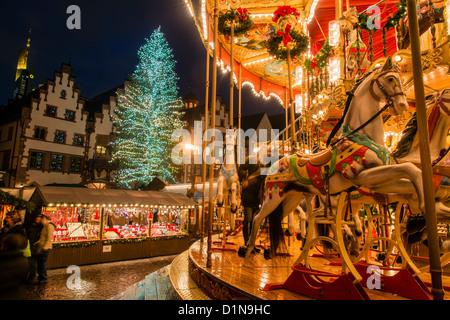Night view of the Romer, Römerberg, with merry-go-round lights and Christmas tree, Frankfurt am Main, Hesse, Germany - Stock Photo