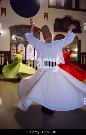 Male Sufi Whirling Dervish in white at a Sema Ceremony with musicians and women at Istanbul train station Turkey - Stock Photo