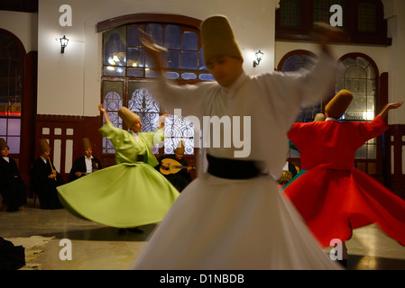 Spinning male and female Whirling Dervishes in a Sema Ceremony with musicians at Istanbul train station Turkey - Stock Photo