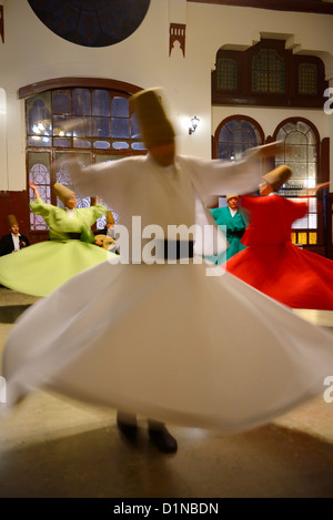 Spinning man with female Whirling Dervishes in a Sema Ceremony with musicians at Istanbul train station Turkey - Stock Photo
