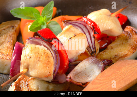 Pan roasted vegetables and chicken skewer in a frying pan - Stock Photo