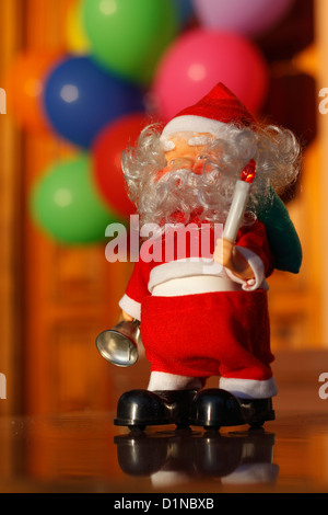 A little Santa Claus toy in front a colorful group of out of focus balloons. - Stock Photo