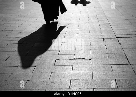 Shadow of a Muslim woman and two men walking on Eyup Sultan Boulevard Istanbul Turkey - Stock Photo