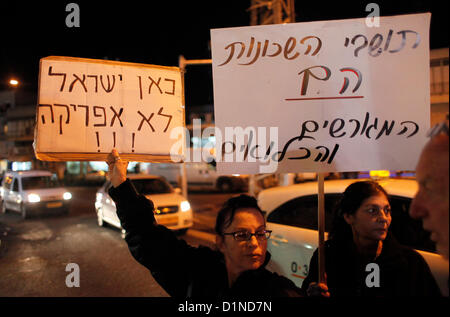 An Israeli woman holds a cardboard sign in Hebrew which reads 'This is Israel not Africa' during a demonstration - Stock Photo