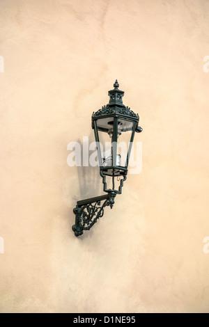 Old street light closeup on stone wall in Prague - Stock Photo