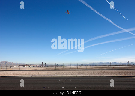 plane taking off into blue sky with contrails at the end of the runway at mccarran international airport Las Vegas - Stock Photo