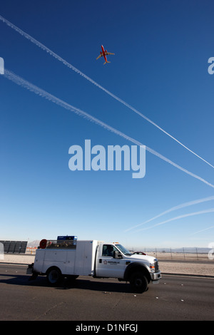 plane taking off into blue sky with contrails at the end of the runway over passing truck at mccarran international - Stock Photo
