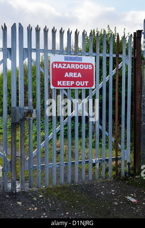 Sign on a security gate warning 'Hazardous area. Keep out' - Stock Photo