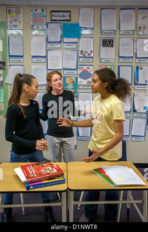An intermediate school teacher resolves a dispute between two students in her San Clemente, California, classroom. - Stock Photo
