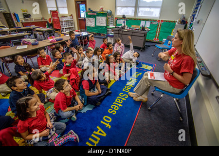 A volunteer teacher sponsored by her employer reads to Hispanic elementary schoolchildren in Santa Ana, CA. - Stock Photo