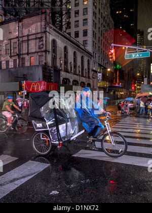 A raincoated Hispanic pedicab taxi driver waves a V-sign while riding down Broadway in Times Square, New York City. - Stock Photo