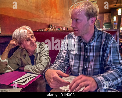 An older woman exemplifies the 'cougar,' a woman who favors a much younger man in Brooklyn, New York, restaurant. - Stock Photo