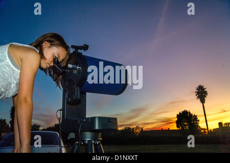 At dusk an eight-year-old girl looks through the eyepiece of a catadioptric astronomical telescope in her California - Stock Photo