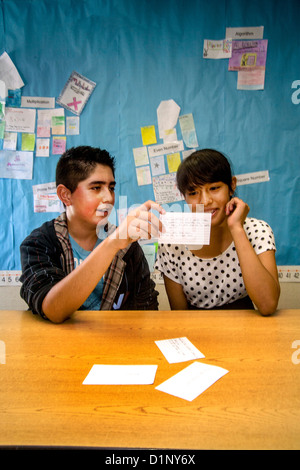 A Hispanic junior high school student tests his classmate's math skills using flash cards in a San Clemente, CA, - Stock Photo