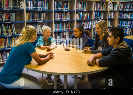 A junior high school counselor meets with a multiethnic group of students in a San Clemente, CA, school library. - Stock Photo