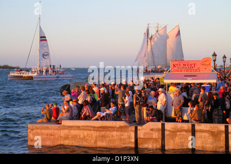 Florida Key West Florida Keys Gulf of Mexico water Mallory Square Sunset Celebration crowd watching catamaran sailing - Stock Photo