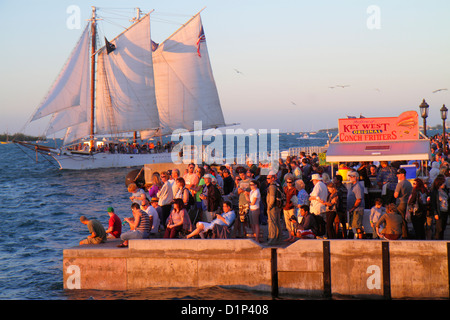 Florida Key West Florida Keys Gulf of Mexico water Mallory Square Sunset Celebration crowd watching 2-masted sailing - Stock Photo
