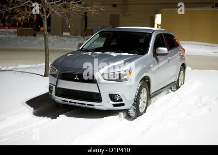 car parked in deepening snow in outdoor parking lot in Saskatoon Saskatchewan Canada - Stock Photo