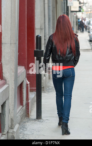 Rear view of a woman walking on a sidewalk, Ville-Marie, Montreal, Quebec, Canada - Stock Photo
