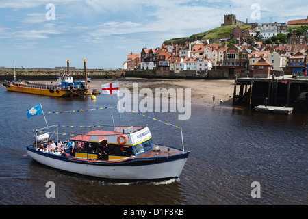 Pleasure boat entering Whitby harbour, North Yorkshire, England - Stock Photo