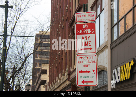 Several traffic signs in a post outside a Subway restaurant in Philadelphia, Pennsylvania, showing some warnings. - Stock Photo