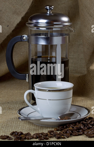 A cup of coffee on hessian with a cafetiere and beans