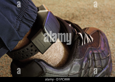 Security electronic tag on a tagged criminal - Stock Photo