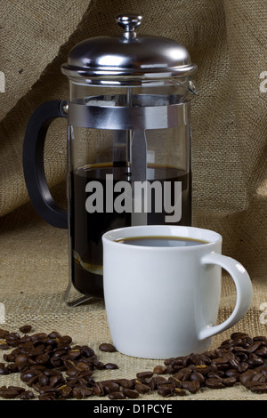 A mug of coffee on a hessian background with beans and a cafetiere
