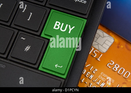 Buy Enter Key on a modern laptop qwerty keyboard with bank smart card underneath to represent online shopping - Stock Photo