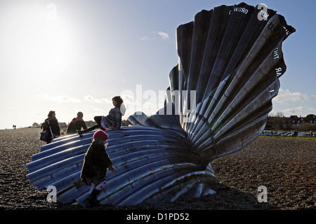 Children playing on the Scallop sculpture on Aldeburgh beach,Suffolk,UK. The structure celebrates composer Benjamin - Stock Photo