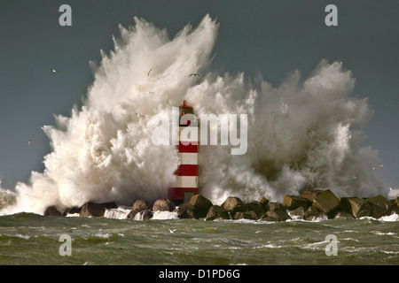 The Netherlands, IJmuiden, Storm. Waves crash against lighthouse or beacon. - Stock Photo