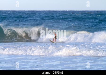 Surfer riding pacific ocean waves off the island coast of Kauai, Hawaii, USA. - Stock Photo