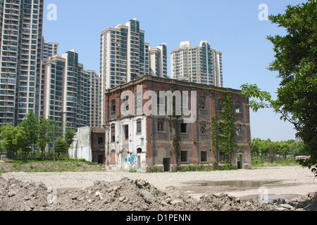 An old derelict warehouse in the centre of Shanghai with modern apartment buildings being built all around it. - Stock Photo