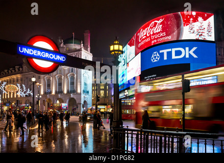 Busy People and a blurred Red London bus on a Busy night near Piccadilly Circus Underground Station Sign Central - Stock Photo