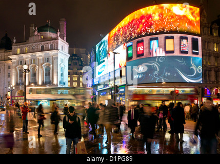 People and London buses on a Busy night in Piccadilly Circus Central London England GB UK EU Europe - Stock Photo