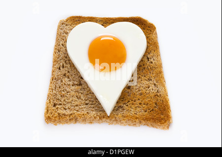 heart shaped cooked egg on a slice of toast to illustrate love of food or healthy eating cholesterol concept - Stock Photo