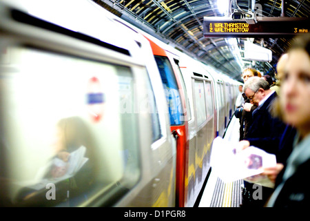 commuters on the platform as a tube train arrives on a northbound Victoria line train to Walthamstow, London - Stock Photo