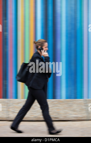 businesswoman using her mobile phone in front of the Tour Moretti at the Esplanade du General de Gaulle in La Defense, - Stock Photo