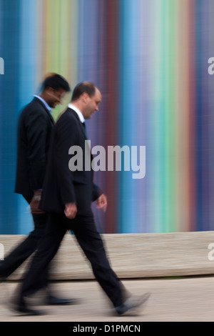 businessmen passing the Tour Moretti at the Esplanade du General de Gaulle in La Defense, Paris - Stock Photo