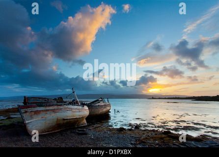 Derelict fishing boats at sunrise on the Isle of Mull in the Inner Hebrides, Scotland, UK, looking towards the Scottish - Stock Photo