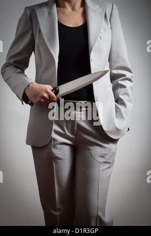 Elegant business woman with a big knife in her hand - Stock Photo