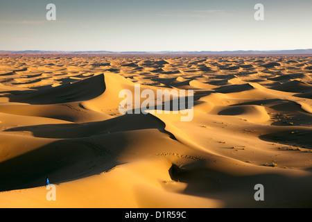 Morocco, M'Hamid, Erg Chigaga sand dunes. Sahara desert. Local Berber man on sand dune, background tourist camp, - Stock Photo