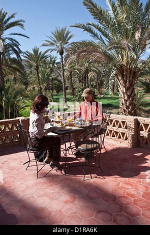Morocco, near Agdz, Hotel Riad Auberge Chez Ait El Caid, kasbah Itrane. Couple having breakfast in oasis. - Stock Photo