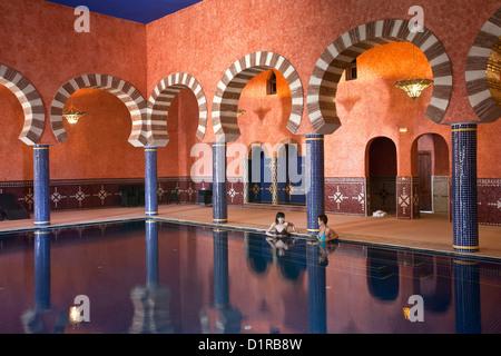 Morocco, M'Hamid el Ghizlane, Hotel Azalay. Indoor swimming pool. Women. - Stock Photo