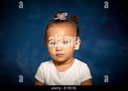 Cute studio portraits of little girl, mixed race under two years old smiling. - Stock Photo
