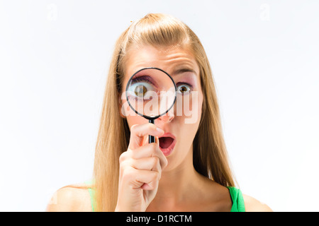 Woman looking through magnifying glass or loupe - Stock Photo