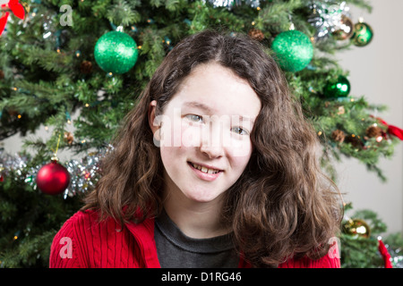 Closeup of young girl smiling with Christmas Tree in Background - Stock Photo
