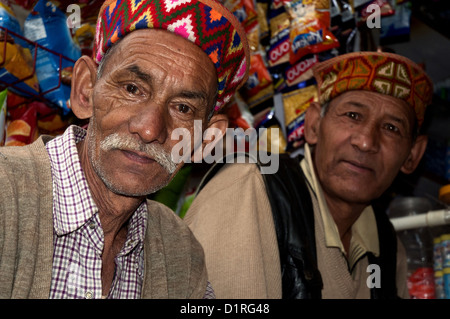 Local men in Old Manali, Himachal Pradesh. They are wearing the traditional caps of the region. - Stock Photo