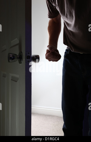 Aggressive male entering a dark room, fist clenched. Face not shown. - Stock Photo