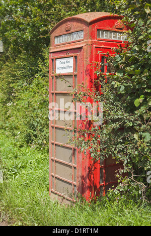 Old telephone box on grass verge appears unused, windows covered in algae - Stock Photo
